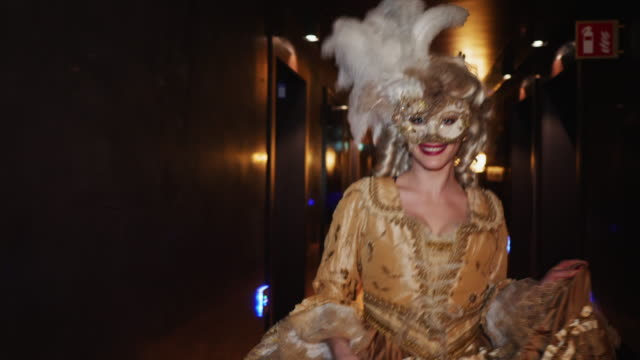 portrait of smiling woman wearing historical clothing and venetian mask running in corridor at night - allegro video stock e b–roll