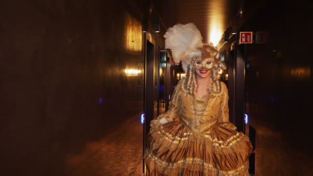 portrait of smiling woman wearing historical clothing and venetian mask walking backwards in corridor at night - historical clothing stock videos & royalty-free footage