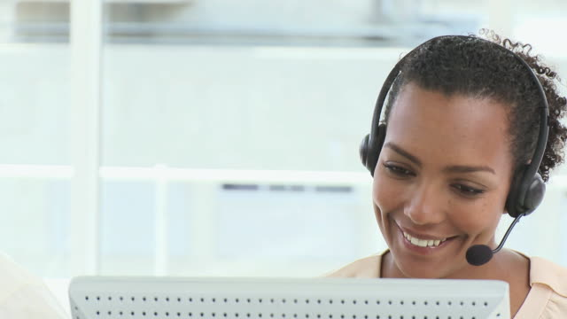 cu pan portrait of smiling woman with headset in front of computer / cape town, western cape, south africa - headset stock videos & royalty-free footage