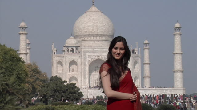 slo mo, ms, portrait of smiling woman with taj mahal in background, agra, uttar pradesh, india - agra stock videos and b-roll footage