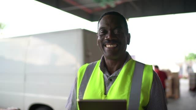 倉庫でデジタルタブレットを使用して笑顔の労働者の肖像画 - 倉庫作業員点の映像素材/bロール