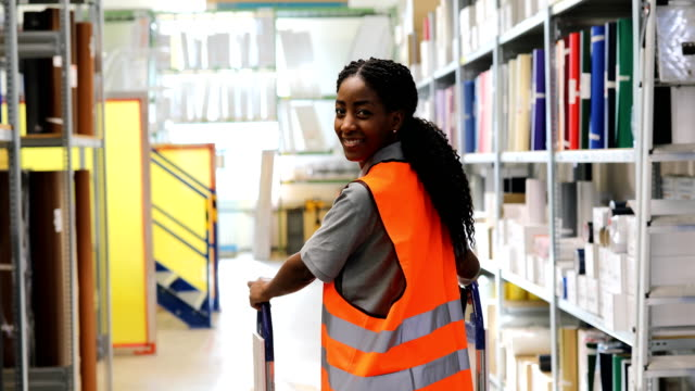 portrait of smiling worker with cart in warehouse - push cart stock videos & royalty-free footage