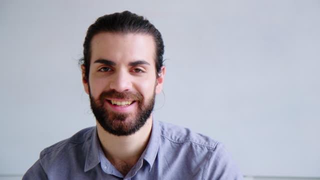 porträt eines lächelnden jungen geschäftsmannes im büro - handsome people stock-videos und b-roll-filmmaterial