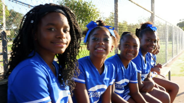 ts portrait of smiling young cheerleaders sitting together on bench in park - cheerleader stock videos & royalty-free footage