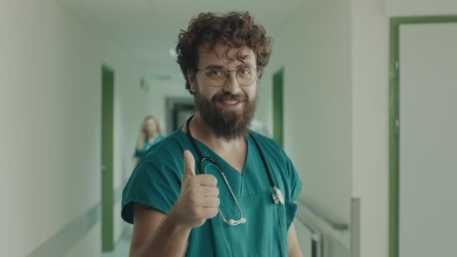 portrait of smiling young doctor showing thumbs up - thumbs up stock videos & royalty-free footage