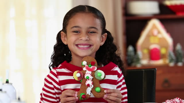 ms portrait of smiling young girl holding gingerbread man cookie / richmond, virginia, usa - decorating stock videos & royalty-free footage
