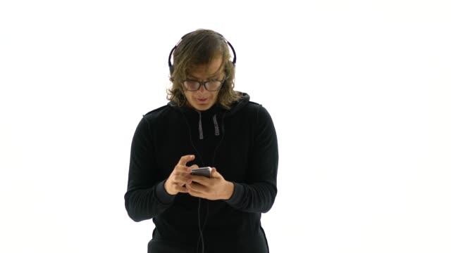 vídeos de stock, filmes e b-roll de retrato do macho novo de sorriso que prende o telefone esperto e a música de escuta - fundo branco