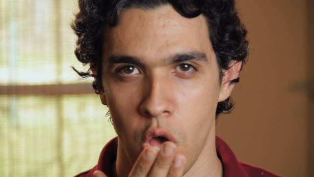 cu portrait of smiling young man blowing kiss and smiling / madison, florida, usa - flirtare video stock e b–roll