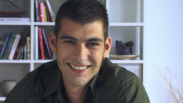 cu, portrait of smiling young man in living room - sideburn stock videos & royalty-free footage