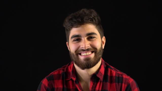 vídeos y material grabado en eventos de stock de retrato de sonriente joven en camisa roja - bien parecido