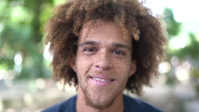 vídeos de stock e filmes b-roll de portrait of smiling young man on the street - barba por fazer