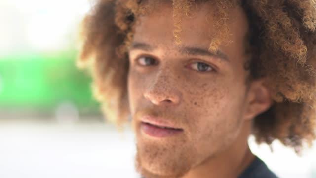 porträt eines lächelnden jungen mannes auf der straße - rotes haar stock-videos und b-roll-filmmaterial