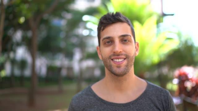 vídeos de stock e filmes b-roll de portrait of smiling young man outdoors - geração millennial