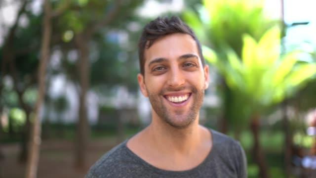 vídeos de stock, filmes e b-roll de retrato de jovem sorridente ao ar livre - handsome people