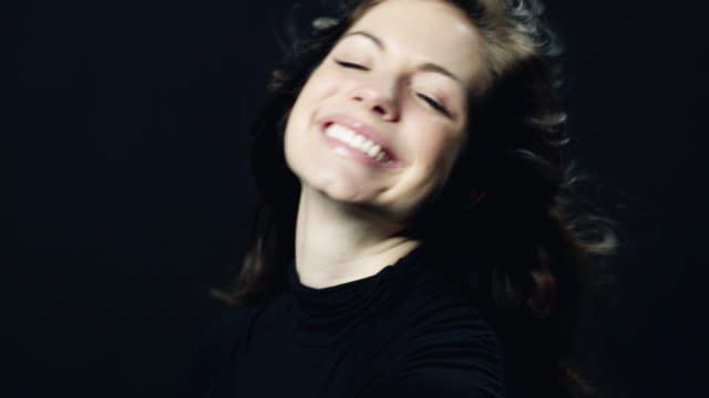 cu portrait of smiling young woman against black background / orem, utah, usa - orem utah stock videos & royalty-free footage