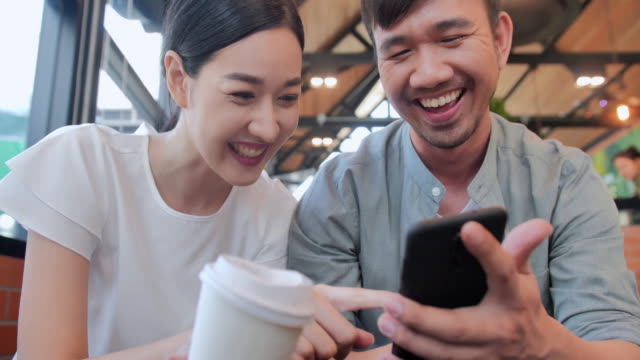 portrait of smiling young woman at a cafe table looking at smartphone with a friend sitting by.technology,friendship,people,lifestyle,vision,business,innovation,global concept.south east and east asia: couple at a café - east asian ethnicity video stock e b–roll