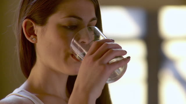 stockvideo's en b-roll-footage met cu portrait of smiling young woman drinking water from glass / brooklyn, new york city, new york, usa - drinkwater
