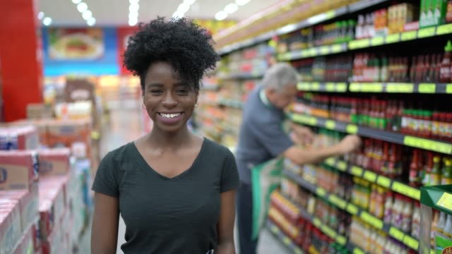 portrait of smiling young woman in supermarket - convenience stock videos & royalty-free footage