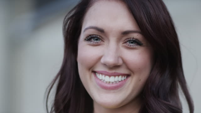 slo mo cu portrait of smiling young woman / pleasant grove, utah, usa - sorridere video stock e b–roll