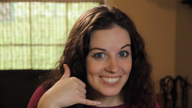 CU Portrait of smiling young woman showing 'call me' hand gesture / Madison, Florida, USA