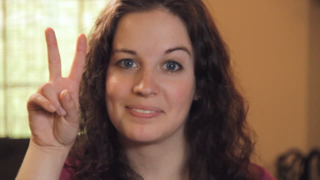 stockvideo's en b-roll-footage met cu portrait of smiling young woman showing peace hand gesture / madison, florida, usa - vredesteken handgebaar