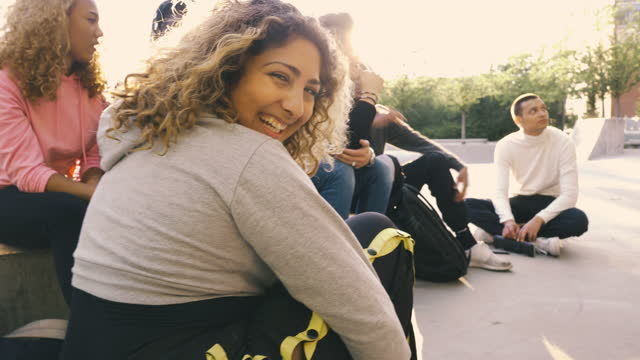 portrait of smiling young woman sitting with friends at skateboard park - looking away stock videos & royalty-free footage