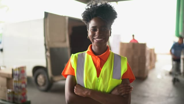 vídeos de stock e filmes b-roll de portrait of smiling young worker at warehouse - afro