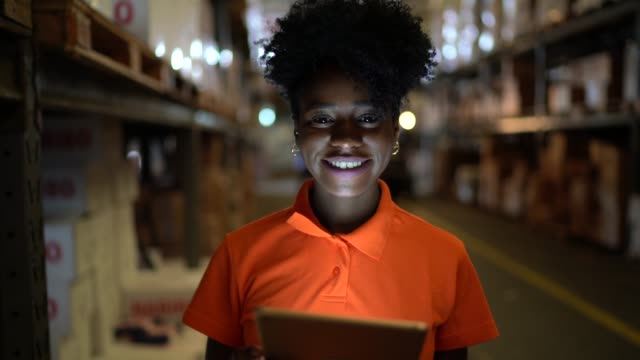 vídeos de stock e filmes b-roll de portrait of smiling young worker using digital tablet at warehouse - trabalhador de armazém