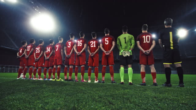 Portrait of soccer players in red uniforms at a rainy stadium