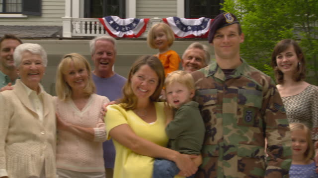 ms portrait of soldier surrounded by smiling multigenerational family in front of suburban home / richmond, virginia - family reunion stock videos and b-roll footage