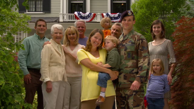 TD MS Portrait of soldier surrounded by smiling multigenerational family in front of suburban home / Richmond, Virginia