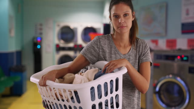 portrait of somber young woman carrying basket of dirty clothes in laundry room - tvättmedel bildbanksvideor och videomaterial från bakom kulisserna