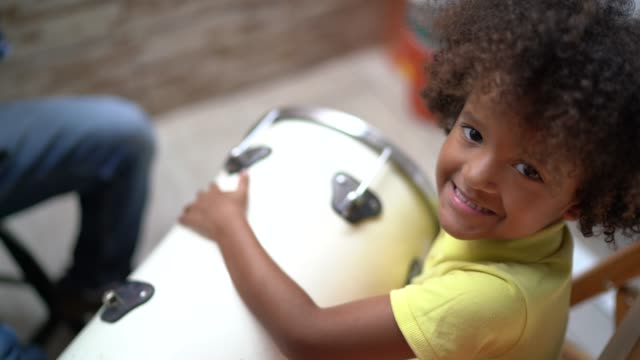 portrait of son playing music at home - with family on background - drum percussion instrument stock videos & royalty-free footage