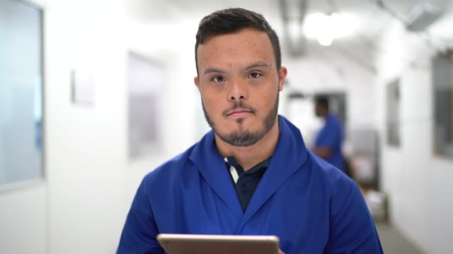 portrait of special needs employee holding a digital tablet in industry - down's syndrome stock videos & royalty-free footage