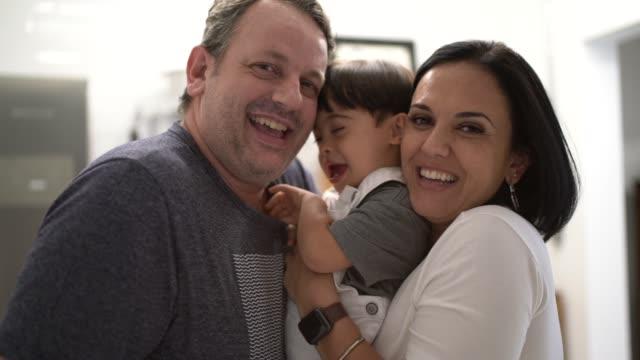 vídeos de stock, filmes e b-roll de retrato dos pais e do filho da síndrome de down em casa - etnia caucasiana