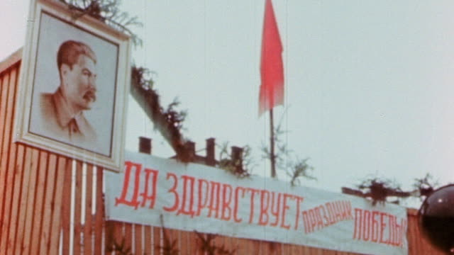 la portrait of stalin and banner in russian language celebrating ve day / germany - ve day stock-videos und b-roll-filmmaterial