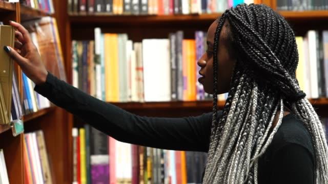 vídeos de stock e filmes b-roll de portrait of student on library - artigo de decoração