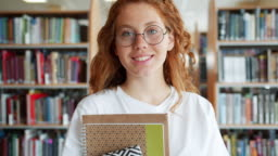Portrait of student pretty girl holding books in university library smiling