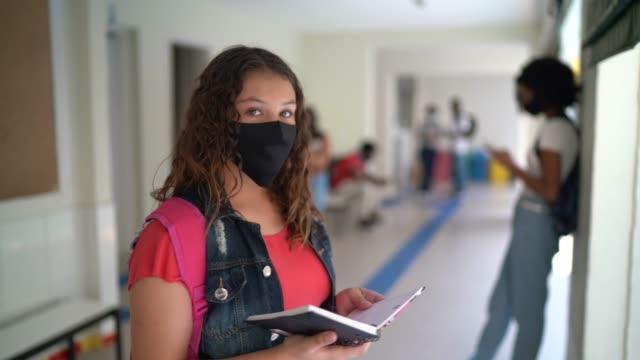vídeos de stock, filmes e b-roll de retrato de estudante usando máscara facial segurando almofada de notas no pátio - note pad