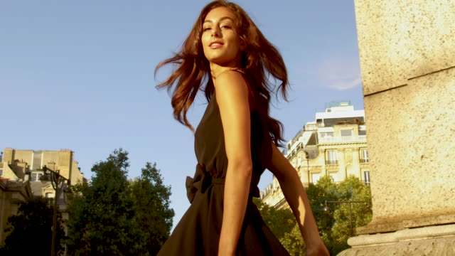 portrait of stylish woman leaning against stone column in paris france, daytime - ドレス点の映像素材/bロール