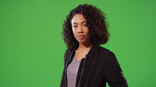 Portrait of stylish woman looking around in black bomber jacket on greenscreen