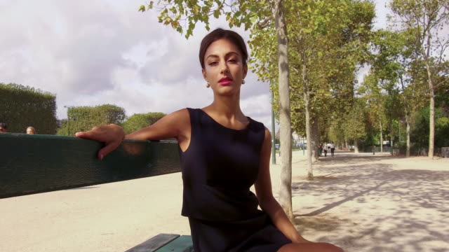 portrait of stylish woman sitting on a park bench in park in front of eiffel tower - 20代点の映像素材/bロール