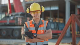 Portrait of Successful Builder / Worker / Contractor Wearing Hard Hat and Safety Vest Standing on a Commercial Building Construction Site, Crosses Arms Confidently. In the Background Crane Machinery