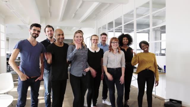 stockvideo's en b-roll-footage met portret van succesvolle business group zwaaiende handen - driekwartlengte