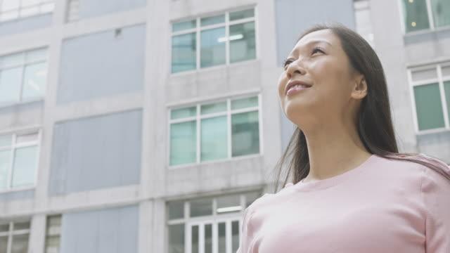 周りを探して都市環境で成功した中国女性の肖像画 - 歯を見せて笑う点の映像素材/bロール