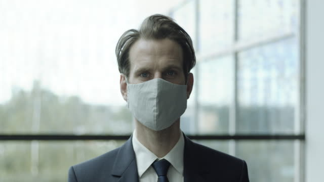 portrait of successful young businessman wearing protective face mask looking into camera in corporate office - full suit stock videos & royalty-free footage