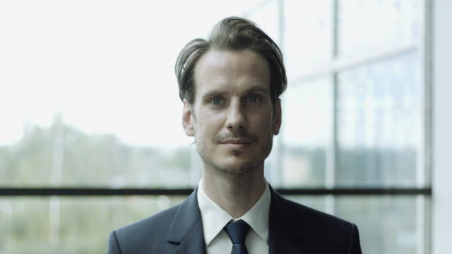 portrait of successful young businessman wearing suit looking into camera in corporate office - full suit stock videos & royalty-free footage