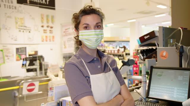 vídeos y material grabado en eventos de stock de retrato del cajero del supermercado con una máscara facial - brazos cruzados