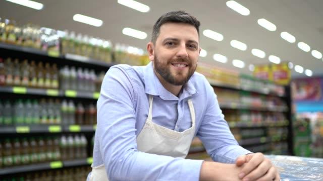 vídeos de stock e filmes b-roll de portrait of supermarket employee or owner - funcionário