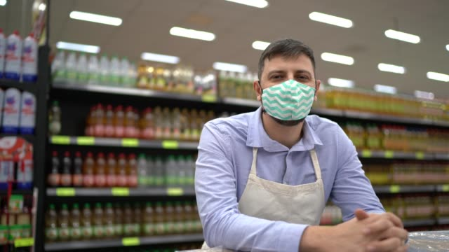 portrait of supermarket employee or owner with face mask - sales occupation stock videos & royalty-free footage